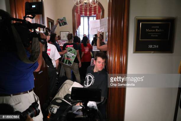 Nick Holzhum blocks the doorway to the offices of Sen Marco Rubio while dozens of other protesters rally inside the office against the Republican...