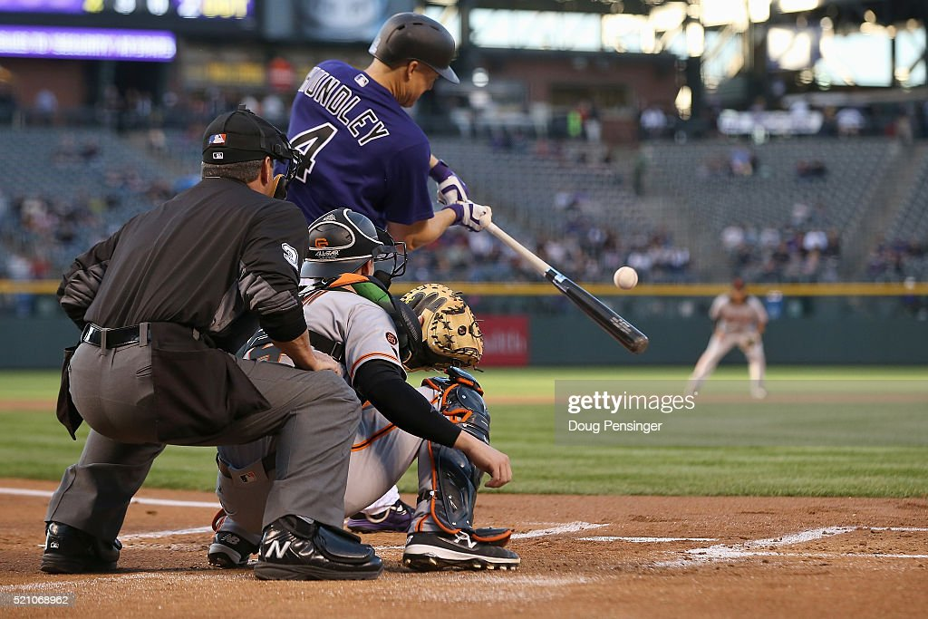 Nick Hundley of the Colorado Rockies takes an at bat as catcher Trevor Brown of the San Francisco Giants backs up the plate and umpire Rob Drake...
