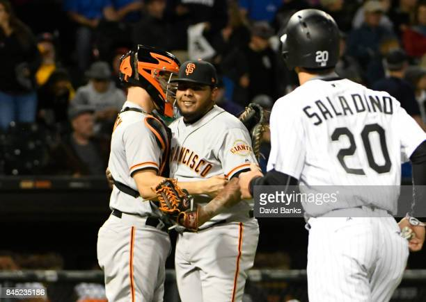 Nick Hundley of the San Francisco Giants and Reyes Moronta of the San Francisco Giants celebrate their win as Tyler Saladino of the Chicago White Sox...