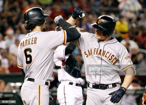 Nick Hundley of the San Francisco Giants is congratulated by teammate Jarrett Parker after hitting a threerun home run against the Arizona...