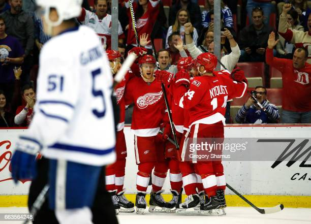 Nick Jensen of the Detroit Red Wings celebrates his second period goal with teammates behind Jake Gardiner of the Toronto Maple Leafs at Joe Louis...