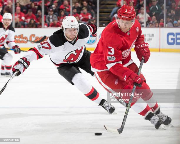 Nick Jensen of the Detroit Red Wings skates with the puck followed by Pavel Zacha of the New Jersey Devils during an NHL game at Joe Louis Arena on...
