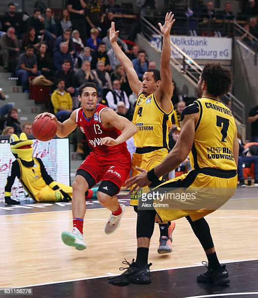 Nick Johnson of Muenchen is challenged by David McCray and Drew Crawford of Ludwigsburg during the easyCredit BBL match between MHP Riesen...