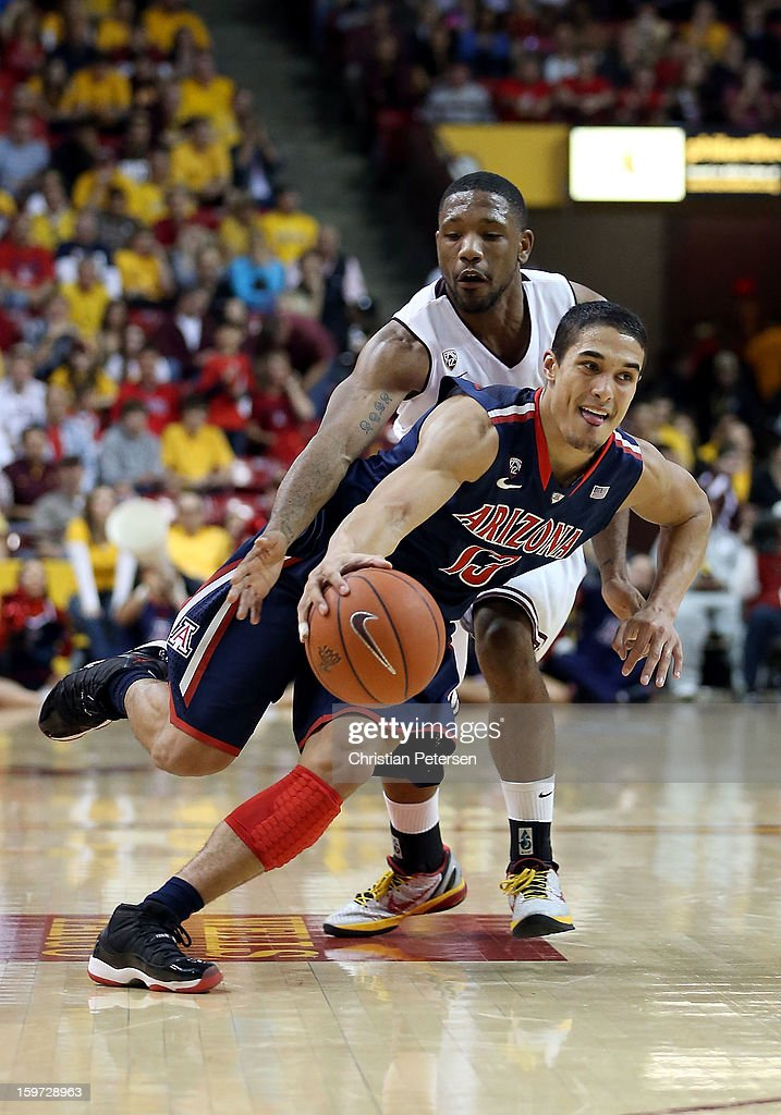 Nick Johnson #13 of the Arizona Wildcats drives the ball past Evan Gordon #10 of the Arizona State Sun Devils during the college basketball game at Wells Fargo Arena on January 19, 2013 in Tempe, Arizona. The Wildcats defeated the Sun Devils 71-54.