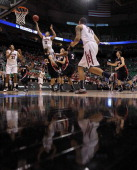 Nick Johnson of the Arizona Wildcats goes up for a shot as he jumps into Reece Chamberlain of the Belmont Bruins in the first half during the second...