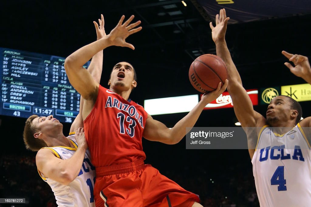 Nick Johnson #13 of the Arizona Wildcats goes up for a shot between David Wear #12 and Norman Powell #4 of the UCLA Bruins in the second half during the semifinals of the Pac-12 tournament at the MGM Grand Garden Arena on March 14, 2013 in Las Vegas, Nevada.