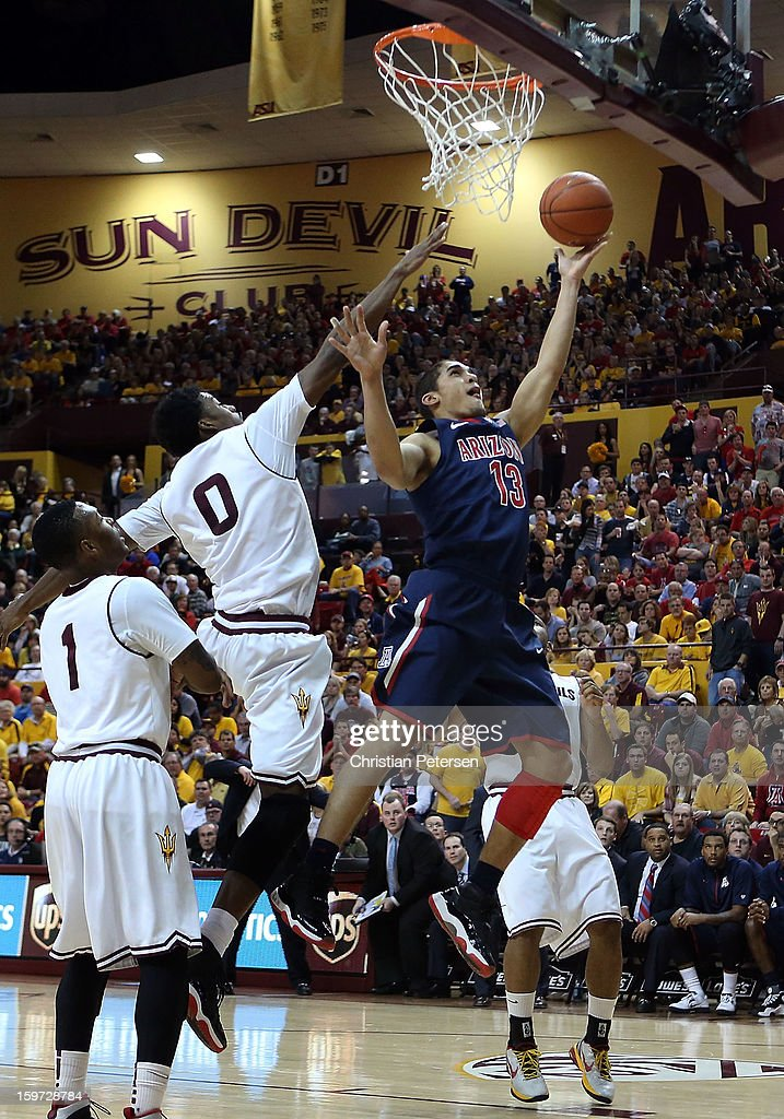 Nick Johnson #13 of the Arizona Wildcats lays up a shot past Carrick Felix #0 of the Arizona State Sun Devils during the second half of the college basketball game at Wells Fargo Arena on January 19, 2013 in Tempe, Arizona. The Wildcats defeated the Sun Devils 71-54.