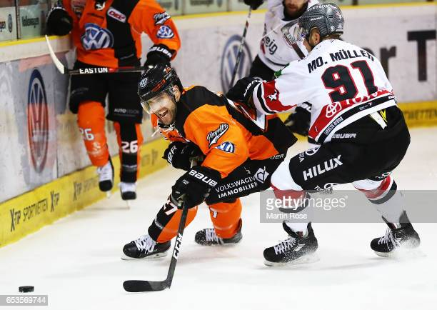 Nick Johnson of the Grizzlys Wolfsburg is challenged by Moritz Mueller of Koelner Haie during the DEL Playoffs Quarter Final Game 4 between the...
