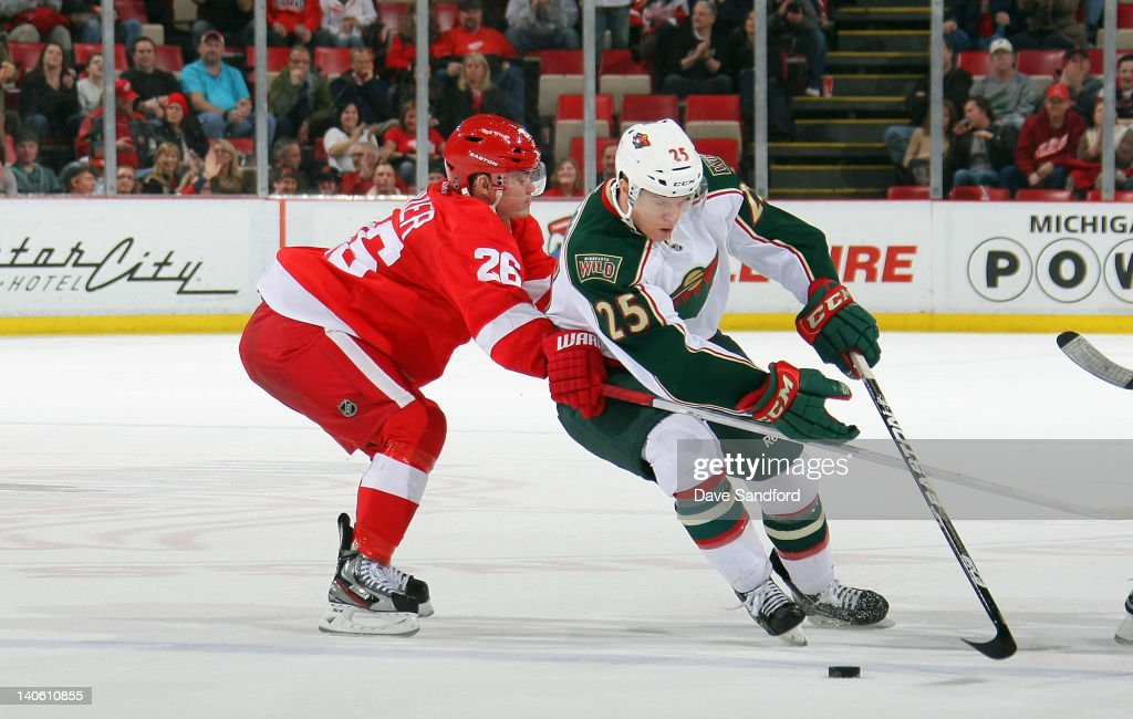 Nick Johnson #25 of the Minnesota Wild carries the puck past a defending <a gi-track='captionPersonalityLinkClicked' href=/galleries/search?phrase=Jiri+Hudler&family=editorial&specificpeople=2118675 ng-click='$event.stopPropagation()'>Jiri Hudler</a> #26 of the Detroit Red Wings during their NHL game at Joe Louis Arena on March 2, 2012 in Detroit, Michigan.