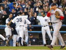 Nick Johnson of the New York Yankees celebrates with teammates Derek Jeter and Jorge Posada after he and Karim Garcia scored on an Alfonso Soriano...