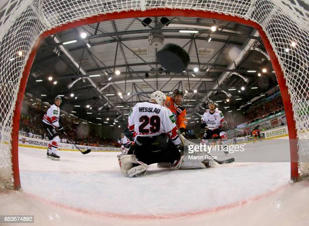 Nick Johnson of Wolfsburg scores the opening goal over Gustaf Wesslau goaltender of Koeln during the DEL Playoffs quarter finals Game 4 between...