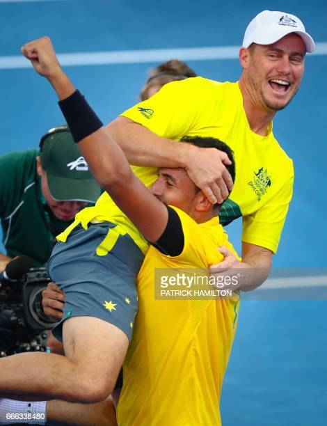 Nick Kyrgios of Australia carries team captain Lleyton Hewitt as they celebrate Australia's victory over the US after Kyrgios' match against Sam...