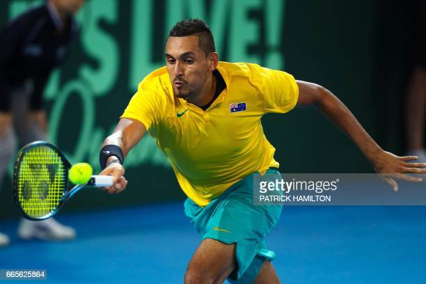 Nick Kyrgios of Australia hits a return to John Isner of the US during their tennis match in the world group quarterfinal Davis Cup clash between...