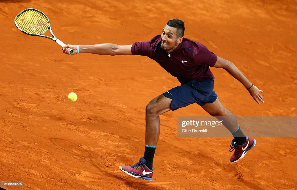 <a gi-track='captionPersonalityLinkClicked' href=/galleries/search?phrase=Nick+Kyrgios&family=editorial&specificpeople=6705178 ng-click='$event.stopPropagation()'>Nick Kyrgios</a> of Australia stretches to play a forehand against Kei Nishikori of Japan in their quarter final round match during day seven of the Mutua Madrid Open tennis tournament at the Caja Magica on May 06, 2016 in Madrid,Spain.