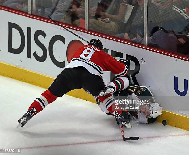 Nick Leddy of the Chicago Blackhawks checks Torrey Mitchell of the Minnesota Wild in Game One of the Western Conference Quarterfinals during the 2013...