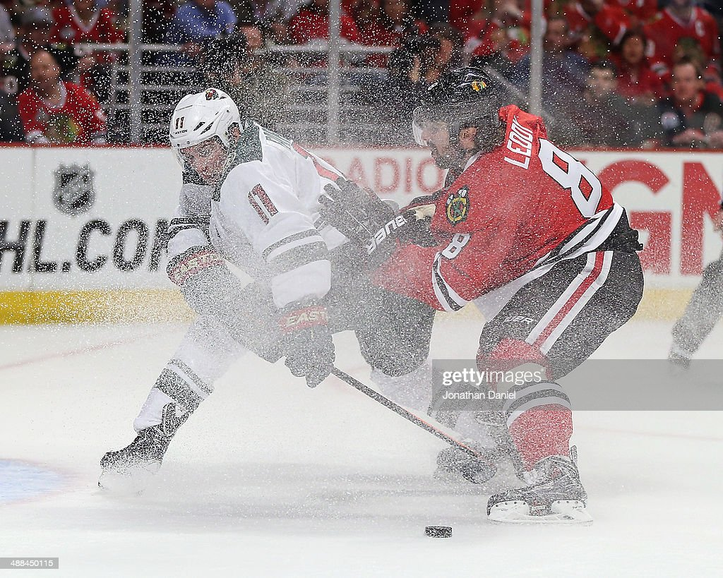 Nick Leddy #8 of the Chicago Blackhawks slows Zach Parise #11 of the Minnesota Wild as he tries to get off a shot in Game One of the Second Round of the 2014 NHL Stanley Cup Playoffs at the United Center on May 2, 2014 in Chicago, Illinois. The Blackhawks defeated the Wild 5-2.