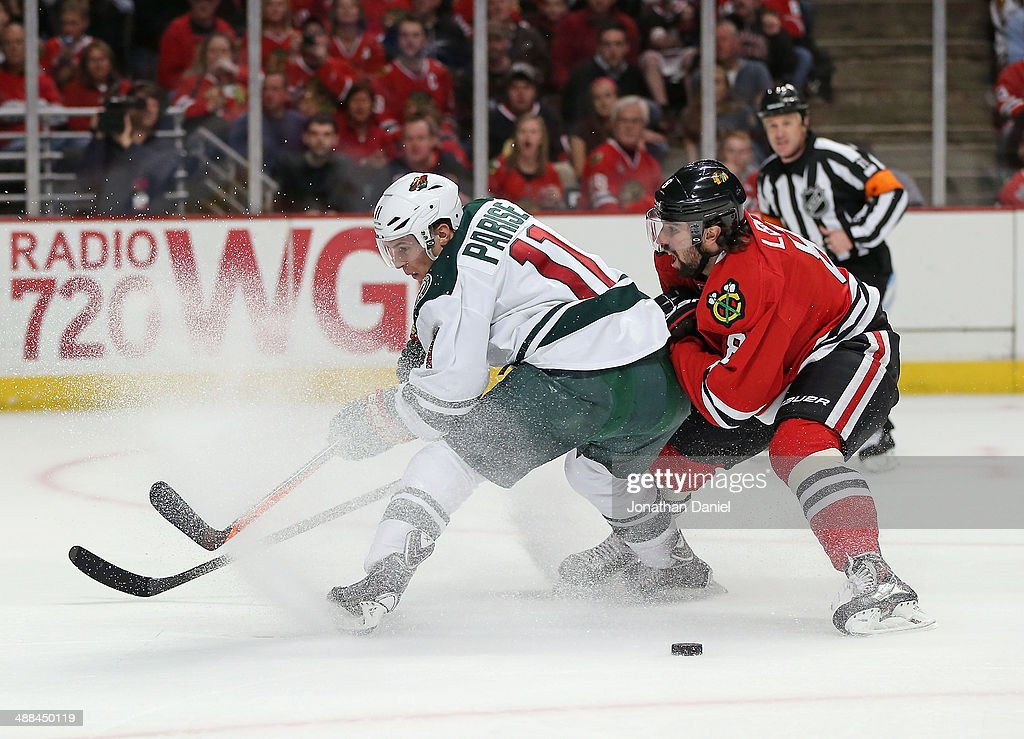 <a gi-track='captionPersonalityLinkClicked' href=/galleries/search?phrase=Nick+Leddy&family=editorial&specificpeople=5894600 ng-click='$event.stopPropagation()'>Nick Leddy</a> #8 of the Chicago Blackhawks slows <a gi-track='captionPersonalityLinkClicked' href=/galleries/search?phrase=Zach+Parise&family=editorial&specificpeople=213606 ng-click='$event.stopPropagation()'>Zach Parise</a> #11 of the Minnesota Wild as he tries to get off a shot in Game One of the Second Round of the 2014 NHL Stanley Cup Playoffs at the United Center on May 2, 2014 in Chicago, Illinois. The Blackhawks defeated the Wild 5-2.
