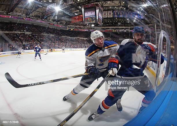 Nick Leddy of the New York Islanders is hit by David Backes of the St Louis Blues at the Nassau Veterans Memorial Coliseum on December 6 2014 in...