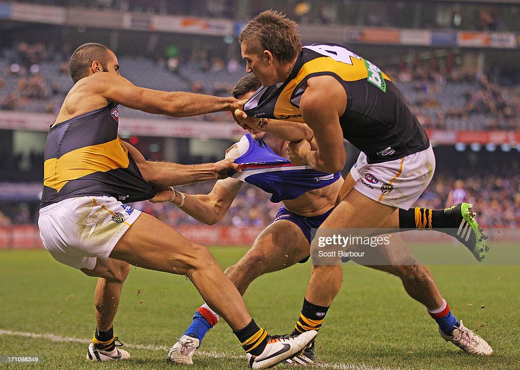 Nick Lower of the Bulldogs and Dustin Martin and Bachar Houli of the Tigers wrestle during the round 13 AFL match between the Western Bulldogs and the Richmond Tigers at Etihad Stadium on June 22, 2013 in Melbourne, Australia.