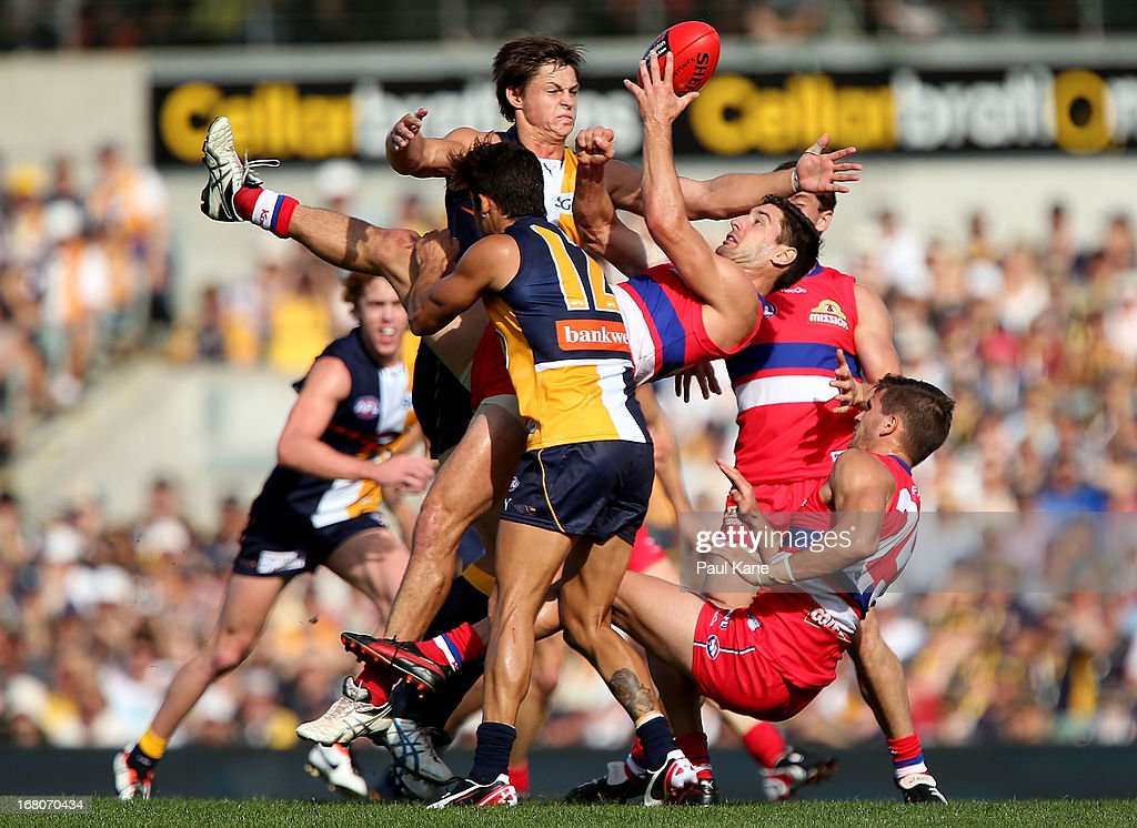 Nick Lower of the Bulldogs gets his handball away while being tackled by Sharrod Wellingham of the Eagles during the round six AFL match between the West Coast Eagles and the Western Bulldogs at Patersons Stadium on May 5, 2013 in Perth, Australia.