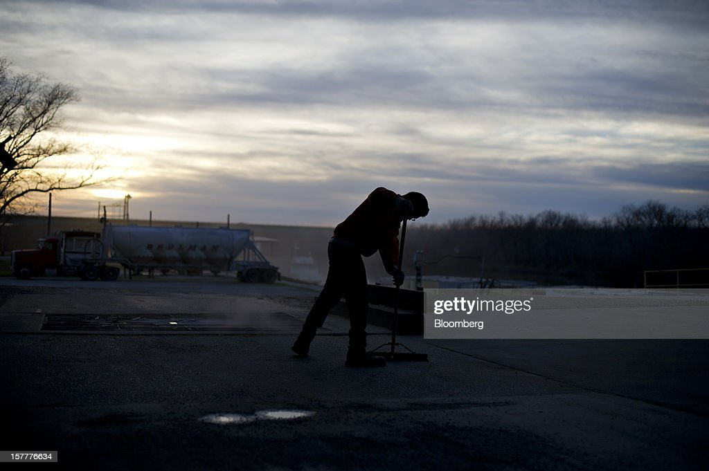Nick Maddox sweeps near a grate covering a delivery pit at the Gateway FS elevator in Evansville, Illinois, U.S., on Wednesday, Dec. 5, 2012. U.S. farmers, facing aftershocks of the worst drought in 50 years, are improvising alternative plans for corn, soybeans and other grains that won't be moving to world markets as the Mississippi River dries up. Photographer: Daniel Acker/Bloomberg via Getty Images