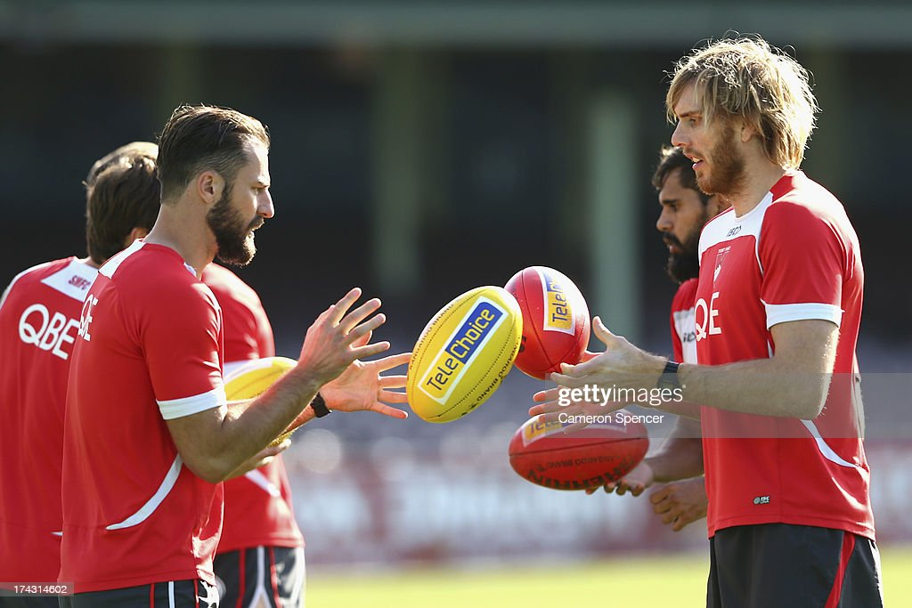 Nick Malceski and Lewis Roberts-Thomson hand-pass during a Sydney Swans AFL training session at Sydney Cricket Ground on July 24, 2013 in Sydney, Australia.