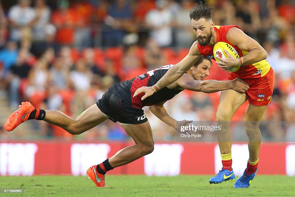 Nick Malceski of the Suns is tackled during the round one AFL match between the Gold Coast Suns and the Essendon Bombers at Metricon Stadium on March...