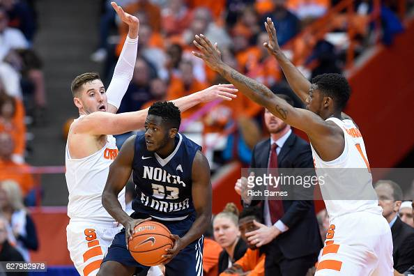Nick Malonga of the North Florida Ospreys controls the ball as Tyler Lydon and Frank Howard of the Syracuse Orange defend during the first half at...