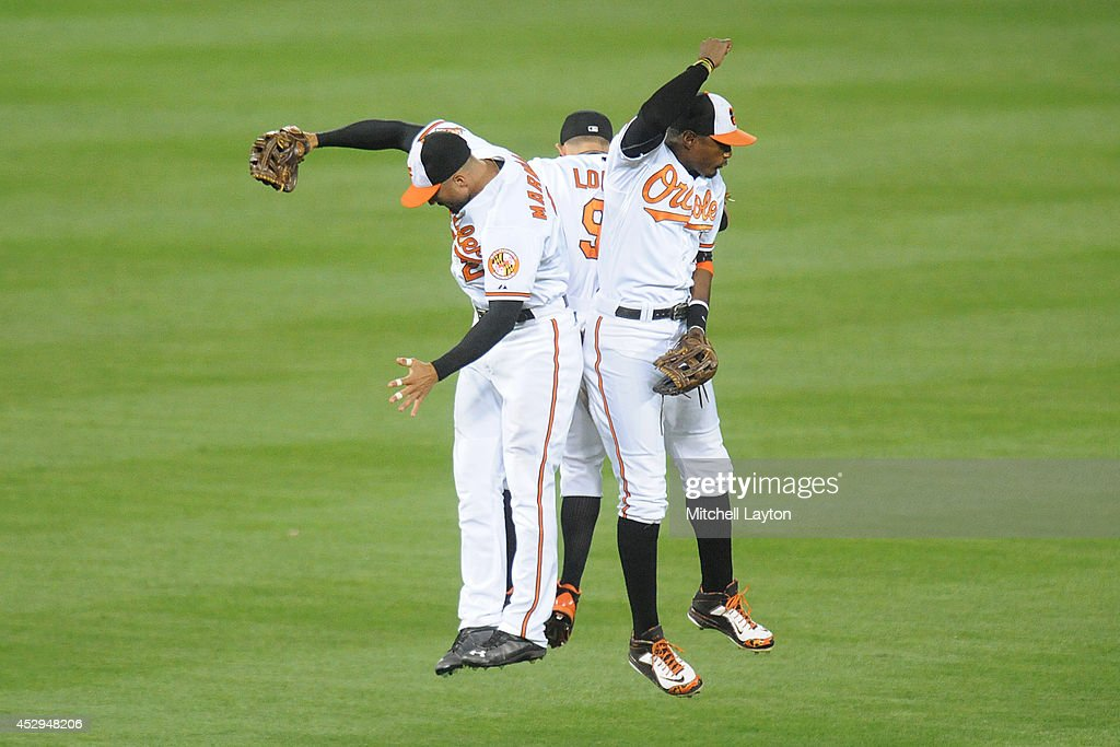 Nick Markakis #21 (L), David Lough #9 and Adam Jones #10 of the Baltimore Orioles celebrate a win after a baseball game against the Los Angeles Angels of Anaheim on July 30, 2014 at Nationals Park in Baltimore, Maryland. The Orioles won 4-3.