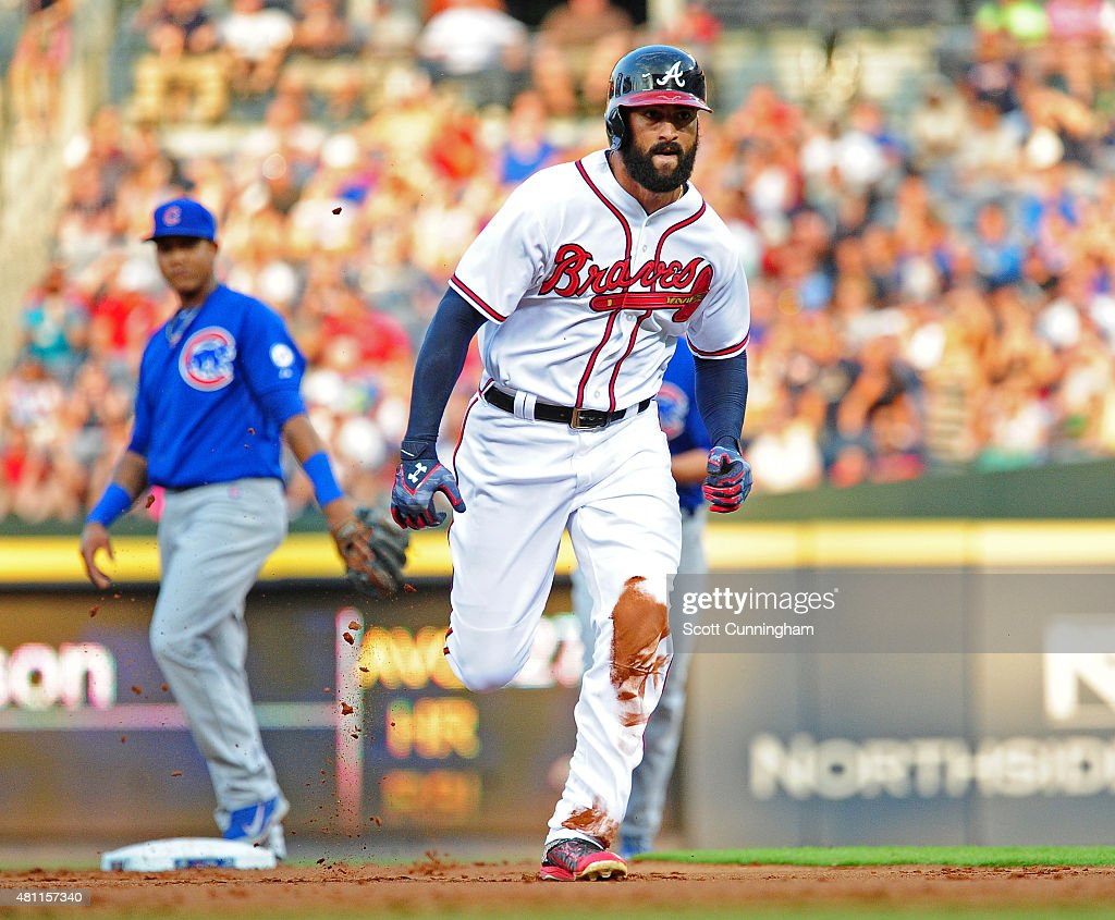 Nick Markakis of the Atlanta Braves heads to third base after a throwing error by Kyle Schwarber of the Chicago Cubs during the first inning at...