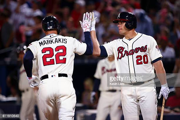 Nick Markakis of the Atlanta Braves is congratulated by Anthony Recker after hitting a home run against the Detroit Tigers during the sixth inning at...