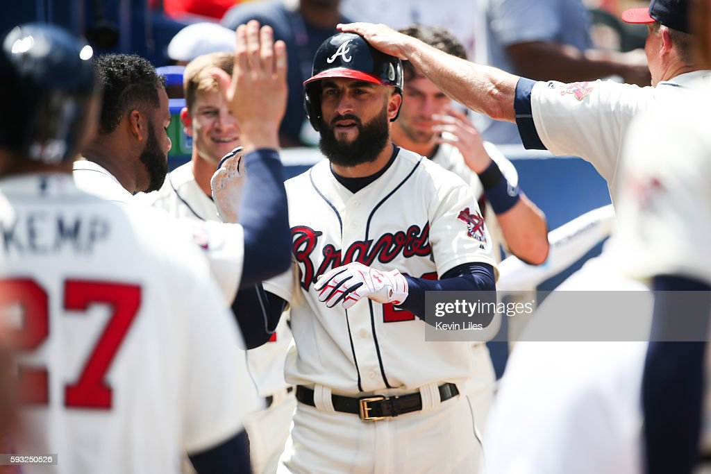 Nick Markakis of the Atlanta Braves is congratulated by teammates after scoring against the Washington Nationals during the third inning at Turner...