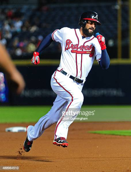 Nick Markakis of the Atlanta Braves rounds third base to score a first inning run against the Philadelphia Phillies at Turner Field on September 18...