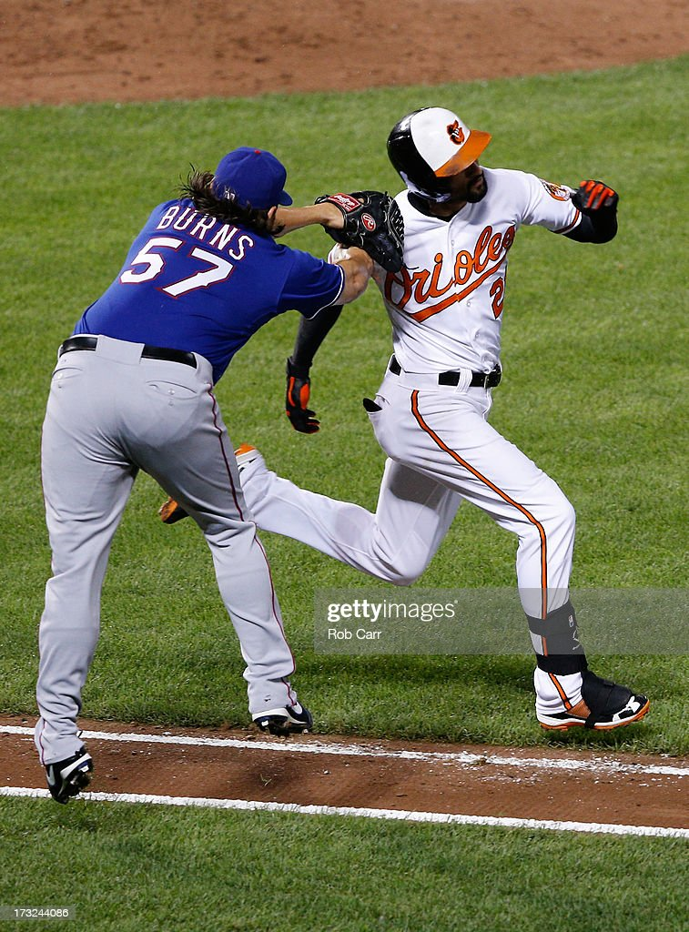 Nick Markakis #21 of the Baltimore Orioles avoids the tag of pitcher Cory Burns #57 of the Texas Rangers to reach first base on an infield single during the seventh inning of the Orioles 6-1 win at Oriole Park at Camden Yards on July 10, 2013 in Baltimore, Maryland.
