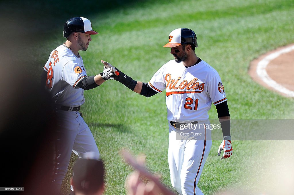 Nick Markakis #21 of the Baltimore Orioles celebrates with Steve Pearce #28 after scoring in the fifth inning against the Boston Red Sox at Oriole Park at Camden Yards on September 29, 2013 in Baltimore, Maryland. Baltimore won the game 7-6.