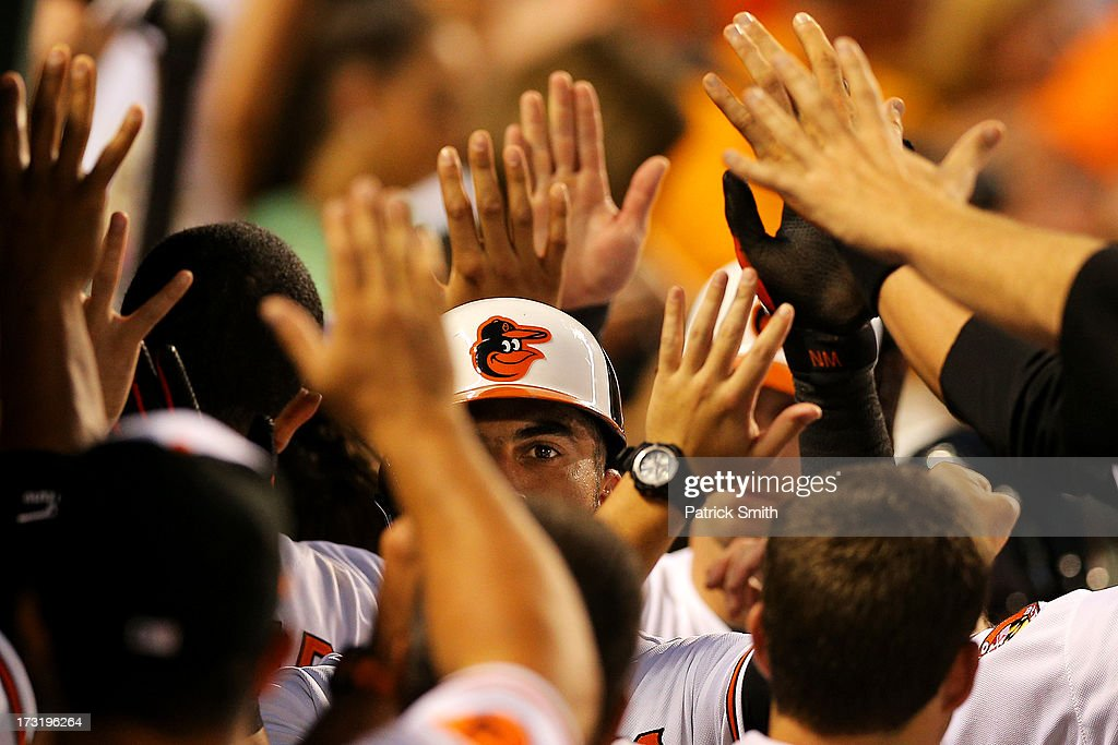 <a gi-track='captionPersonalityLinkClicked' href=/galleries/search?phrase=Nick+Markakis&family=editorial&specificpeople=614708 ng-click='$event.stopPropagation()'>Nick Markakis</a> #21 of the Baltimore Orioles is greeted in the dugout after scoring off of a single by teammate J.J. Hardy #2 (not pictured) in the fifth inning against the Texas Rangers at Oriole Park at Camden Yards on July 9, 2013 in Baltimore, Maryland. The Texas Rangers won, 8-4.