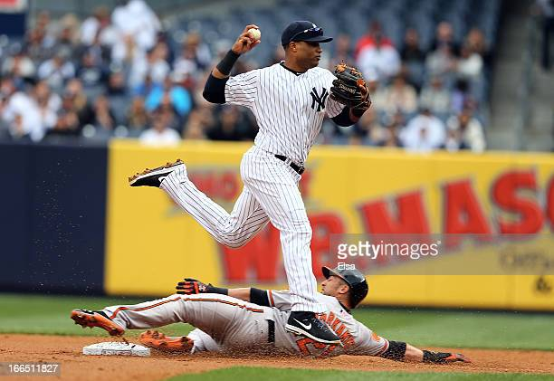Nick Markakis of the Baltimore Orioles is out at second but Robinson Cano of the New York Yankees is unable to turn the double play in the first...