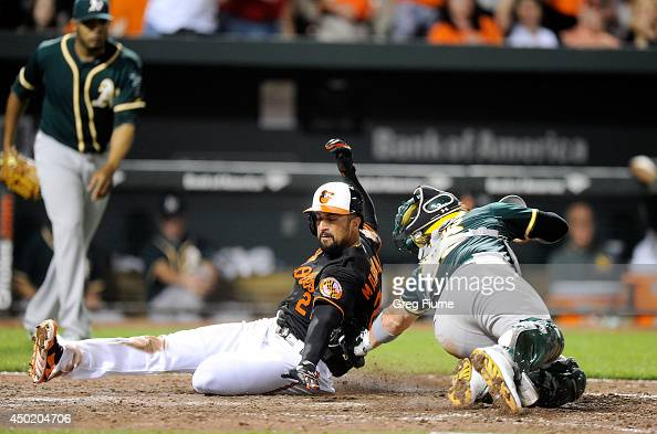 Nick Markakis of the Baltimore Orioles is tagged out at home plate in the tenth inning by Derek Norris of the Oakland Athletics at Oriole Park at...