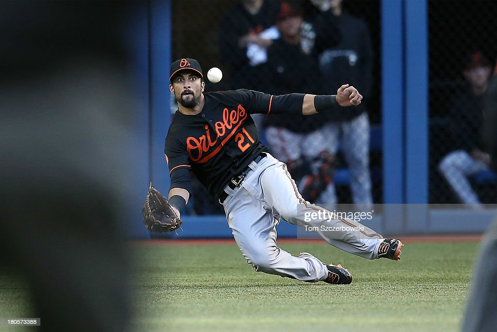 Nick Markakis #21 of the Baltimore Orioles makes a sliding catch to end the eighth inning during MLB game action against the Toronto Blue Jays on September 14, 2013 at Rogers Centre in Toronto, Ontario, Canada.