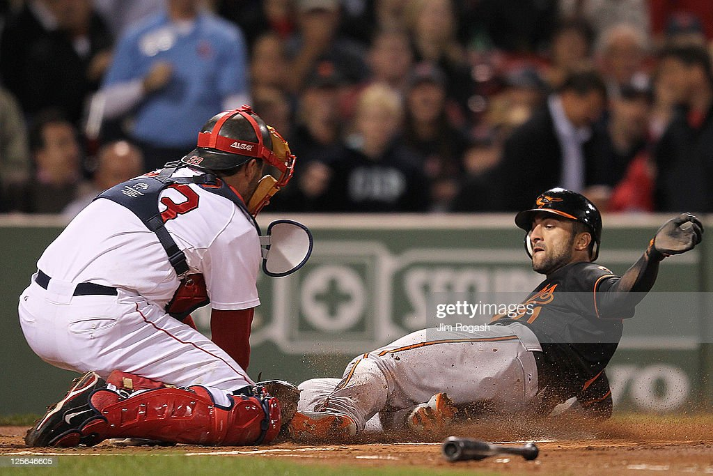 <a gi-track='captionPersonalityLinkClicked' href=/galleries/search?phrase=Nick+Markakis&family=editorial&specificpeople=614708 ng-click='$event.stopPropagation()'>Nick Markakis</a> #21 of the Baltimore Orioles scores a run in the first inning as <a gi-track='captionPersonalityLinkClicked' href=/galleries/search?phrase=Jason+Varitek&family=editorial&specificpeople=171480 ng-click='$event.stopPropagation()'>Jason Varitek</a> #33 of the Boston Red Sox defends in the second game of a doubleheader against the Boston Red Sox at Fenway Park September 19, 2011 in Boston, Massachusetts.