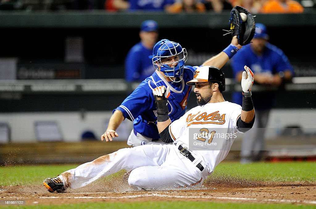 Nick Markakis of the Baltimore Orioles scores in the third inning ahead of the throw to JJ Arencibia of the Toronto Blue Jays at Oriole Park at...