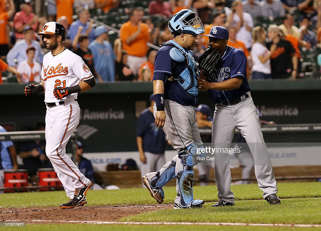 <a gi-track='captionPersonalityLinkClicked' href=/galleries/search?phrase=Nick+Markakis&family=editorial&specificpeople=614708 ng-click='$event.stopPropagation()'>Nick Markakis</a> #21 of the Baltimore Orioles scores on a home run hit by teammate Matt Wieters #32 (not pictured) as catcher <a gi-track='captionPersonalityLinkClicked' href=/galleries/search?phrase=Jose+Molina&family=editorial&specificpeople=206365 ng-click='$event.stopPropagation()'>Jose Molina</a> #28 talks with pitcher <a gi-track='captionPersonalityLinkClicked' href=/galleries/search?phrase=Jamey+Wright+-+Baseball+Player&family=editorial&specificpeople=220683 ng-click='$event.stopPropagation()'>Jamey Wright</a> #35 of the Tampa Bay Rays during the ninth inning of the Rays 7-4 win at Oriole Park at Camden Yards on August 20, 2013 in Baltimore, Maryland.