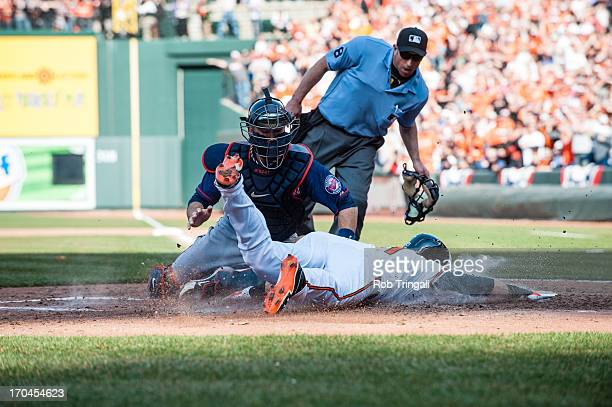Nick Markakis of the Baltimore Orioles slides into home plate as Ryan Doumit of the Minnesota Twins attempts the tag during the game between the two...
