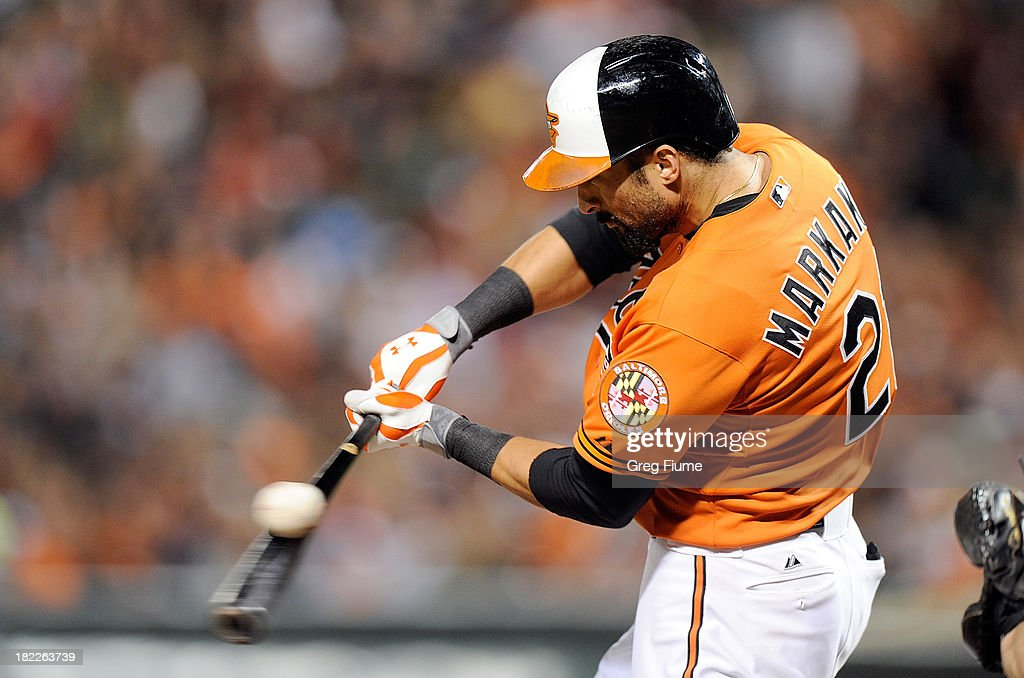 <a gi-track='captionPersonalityLinkClicked' href=/galleries/search?phrase=Nick+Markakis&family=editorial&specificpeople=614708 ng-click='$event.stopPropagation()'>Nick Markakis</a> #21 of the Baltimore Orioles swings and misses for strike three in the eighth inning against the Boston Red Sox at Oriole Park at Camden Yards on September 28, 2013 in Baltimore, Maryland.