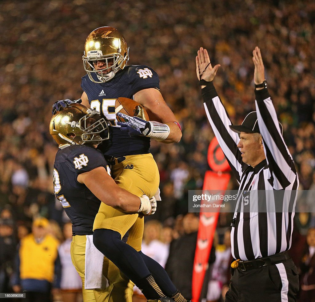 Nick Martin #72 of the Notre Dame Fighting Irish lifts Troy Niklas #85 after Niklas caught a touchdown pass against the University of Southern California Trojans at Notre Dame Stadium on October 19, 2013 in South Bend, Indiana.