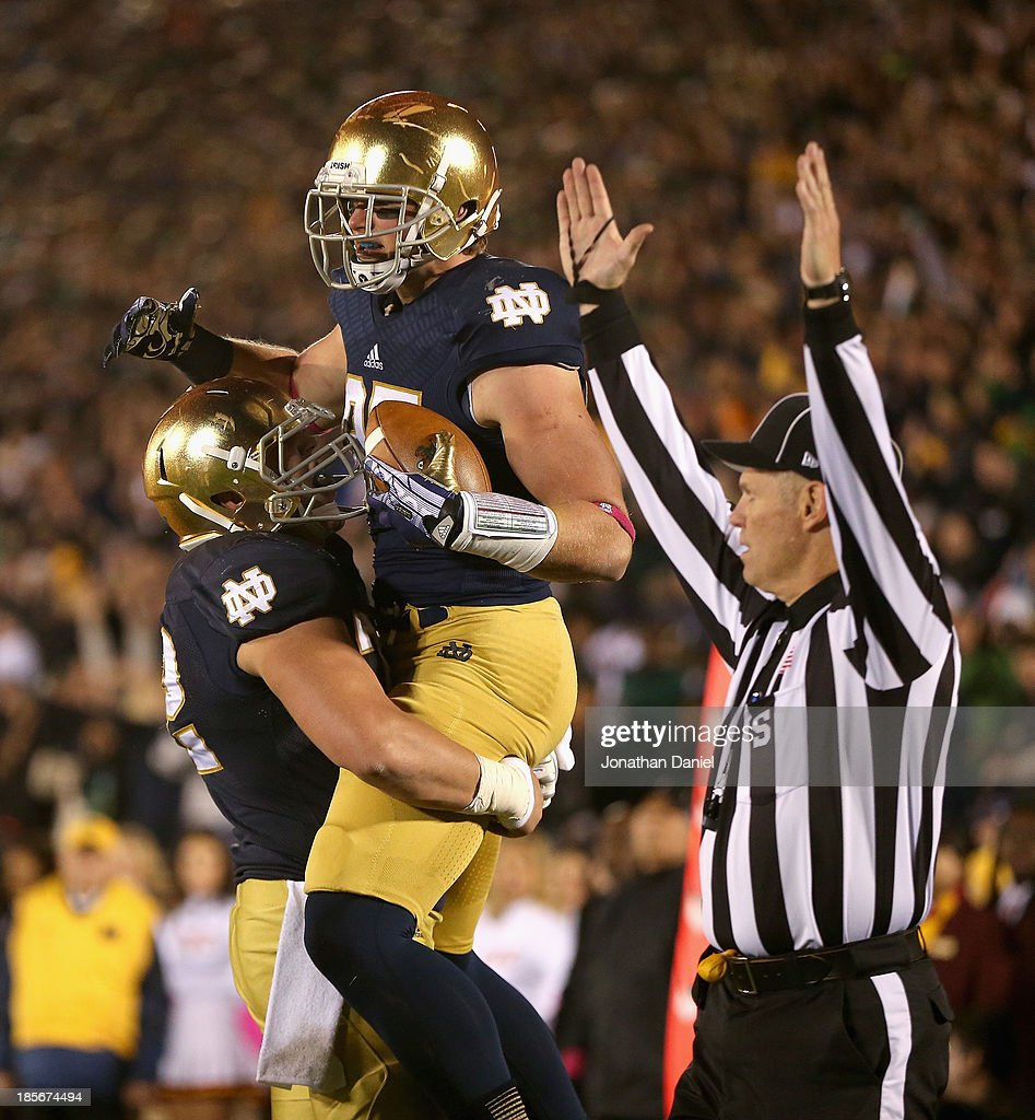 Nick Martin #72 of the Notre Dame Fighting Irish lifts Troy Niklas #85 after Niklas caught a touchdown pass against the University of Southern California Trojans at Notre Dame Stadium on October 19, 2013 in South Bend, Indiana. Notre Dame defeated USC
