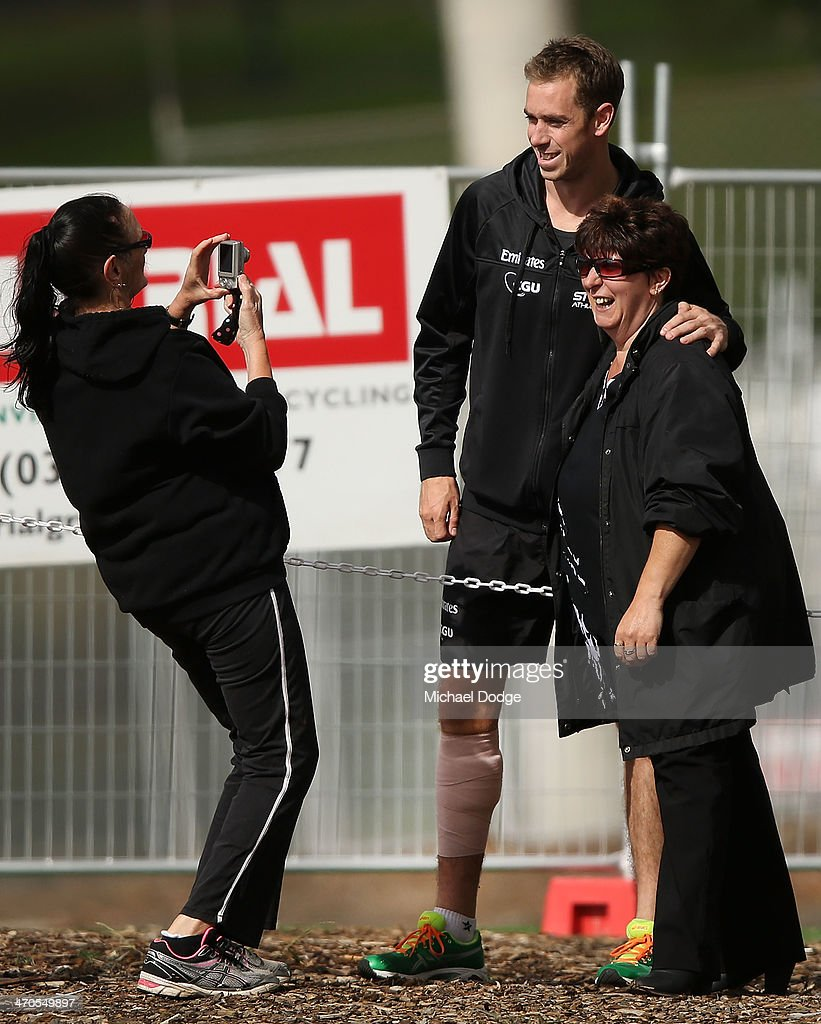 Nick Maxwell is seen posing with fans with a bandaged lower leg during a Collingwood Magpies AFL training session at Olympic Park on February 20, 2014 in Melbourne, Australia.