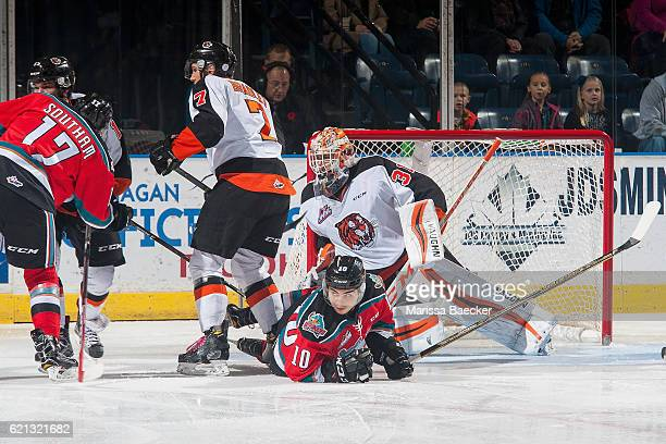 Nick Merkley of the Kelowna Rockets is check to the ice by Matt Bradley in front of the net of Nick Schneider of the Medicine Hat Tigers during first...