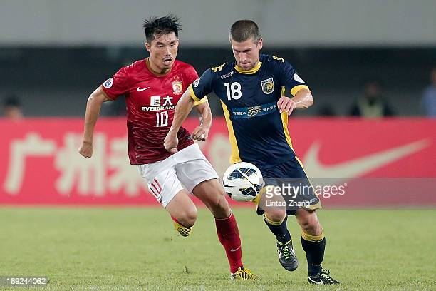 Nick Montgomery of Central Coast challenges Zheng Zhi of Guangzhou Evergrande during the AFC Champions League knockout round match between Guangzhou...