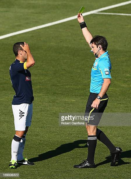 Nick Montgomery of the Mariners reacts as referee Jarred Gillett shows him the yellow card during the round 16 ALeague match between the Melbourne...